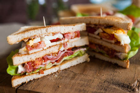 sandwich: Freshly made clubsandwiches served on a wooden chopping board