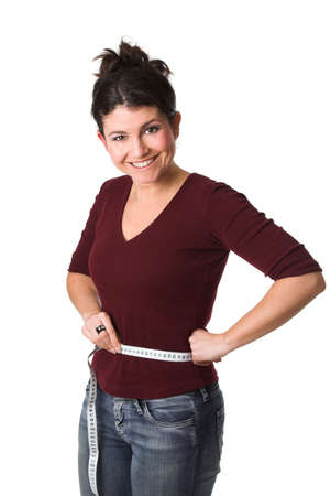 Pretty brunette looking very happy with a measuring tape around her waist Stock Photo