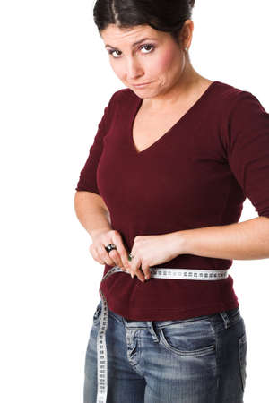 gaining: pretty brunette looking very disappointed while holding a measuring tape around her waist