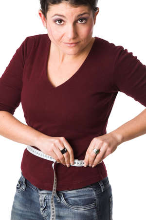 허리의 잘룩 한 선: Pretty brunette measuring her waistline 스톡 사진