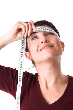 peering: Pretty brunette putting the measuring tape around her head and peering upwards to see if there is any change Stock Photo