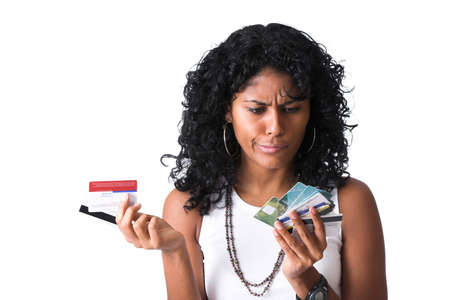 creditcard: Pretty brazilian woman with a stack of creditcard in her hand looking puzzled as to which one to use