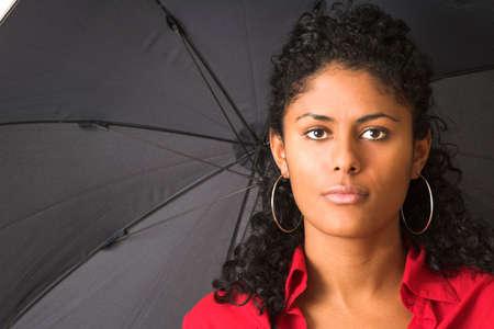Beautiful brazilian woman with black umbrella looking straight into the camera