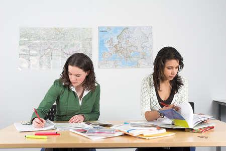trabajando duro: Dos muchachas que se sientan en un escritorio en la escuela que trabaja dif�cilmente Foto de archivo