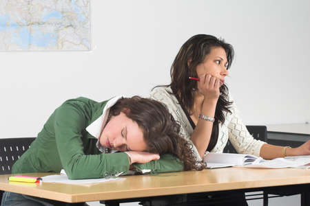 bore: Two teenage girls in class; one has fallen asleep and the other is looking bored out of the window