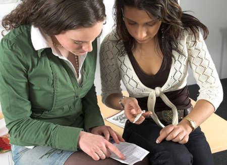 test de grossesse: Deux filles dadolescent sasseyant � c�t� de leachother et v�rifiant lessai de grossesse