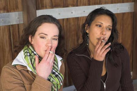 joven fumando: Dos muchachas que fuman afuera en un d�a fr�o del invierno