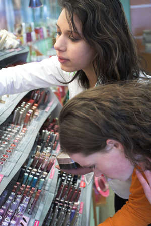 bend over: Two teenage girls bend over a display of make-up in a grocery store Stock Photo
