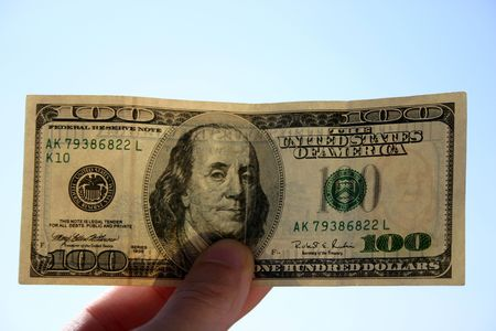 dosh: Checking 100 dollars banknote. In background of sky. Transparent, can see watermarks Stock Photo