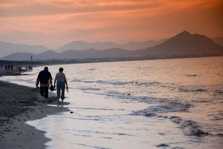 couple walk on the beach on sunset
