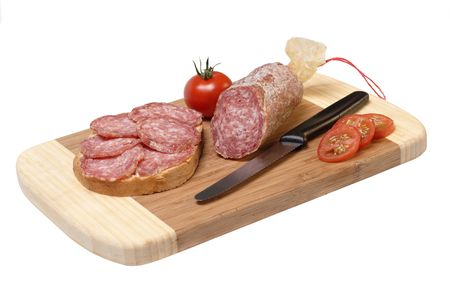 sliced salami with tomato and a knife on wooden plate Stock Photo