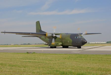 military cargo plane with running engine on taxiway Stock Photo
