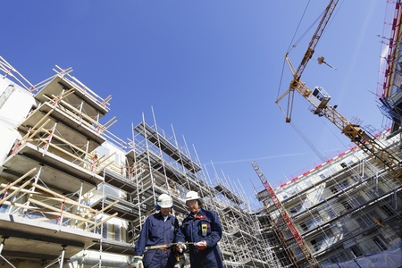building workers surrounded by cranes and scaffolding Stock Photo