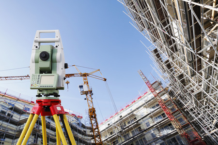 surveying measuring instrument inside large construction site Stock Photo
