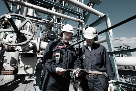 oil and gas workers inside large refinery industry photo