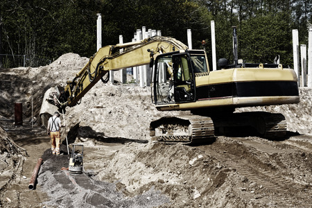 bulldozer, digger and workers in action inside construction plant photo