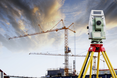 tools construction: surveying measuring instrument aimed at construction-site and cranes Stock Photo