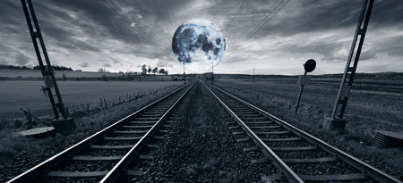 lonely train-track woth a full-moon rising at the horizon