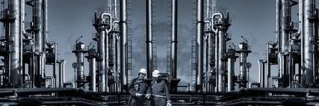 giant oil and gas industry with two engineers in hard-hats, panoramic view