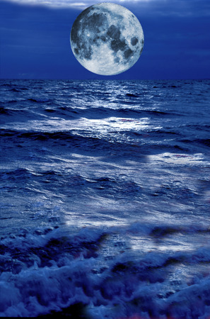 full-moon rising above stormy blue water