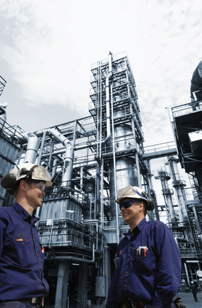 oil workers set against large distillery inside an oil and gas refinery Stock Photo
