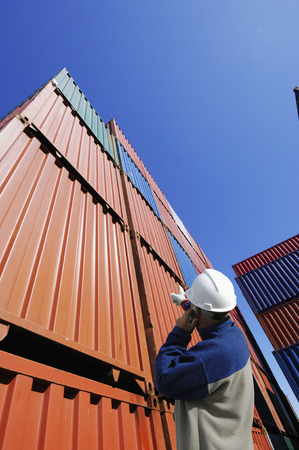 port worker directing stacks of cargo-containers