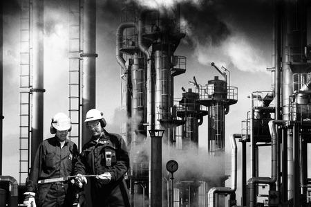 industria petroquimica: dos trabajadores de las refinerías con instalaciones industriales en el fondo Foto de archivo