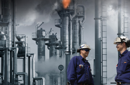 oil and gas industry: two oil and gas workers inside refinery, flames and fire from chimneys
