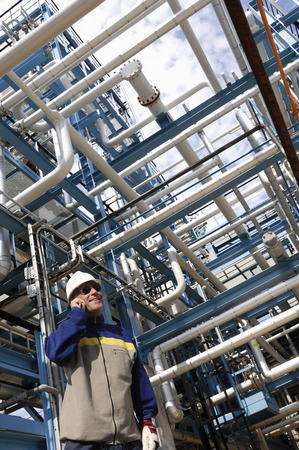refinery worker and giant pipelines construction, energy and power Stock Photo