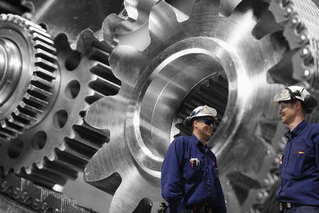 cogwheels: steel mechanics, workers with giant cogwheels and pinions machinery