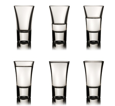 two and two thirds: Six vodka glasses with various level of liquid Stock Photo