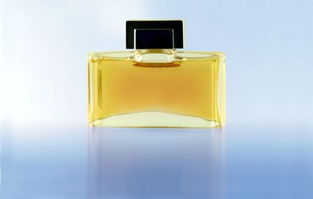 attar: Perfume in a glass bottle against a blue background Stock Photo
