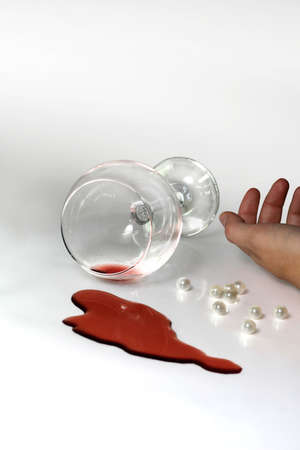perls: A glass of wine fallen on the floor with a dead hand next to it Stock Photo