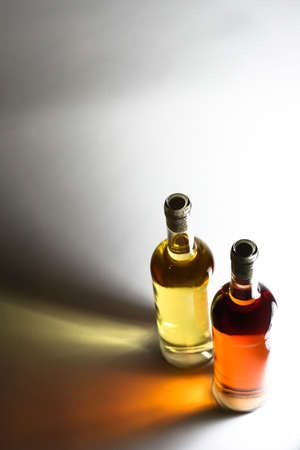 Twho bottles of wine, ros� and white wine in front of a light source, focus is on bottle necks