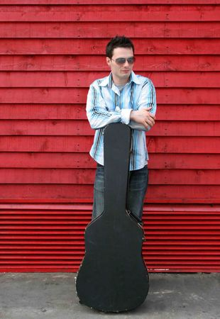 Man leaning on his guitar case photo