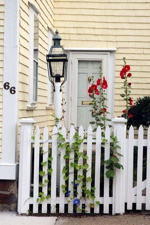 casa colonial: Entranve colonial de la casa con la cerca delantera y el jard�n peque�o