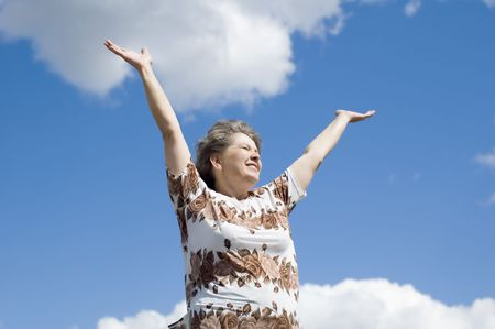 narrowly: woman with hand up on blue sky and clouds