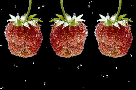 object on black - food strawberry in water photo
