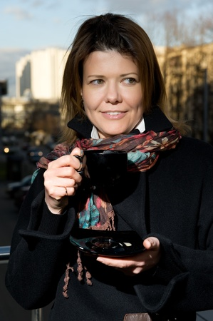 smiling woman on a street in the autumn clothes with a cup of coffee photo
