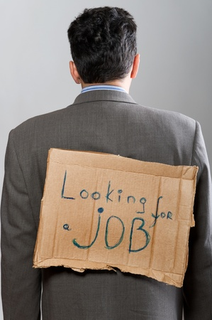 man with cardboard sign Looking job on grey photo