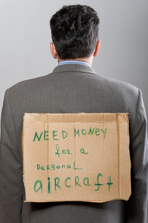 man with cardboard sign Need Money on grey photo