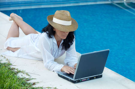 woman working comfortably on the swimming pool Stock Photo