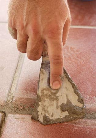 bricklayer: una mano de un alba�il tirando cemento para baldosas