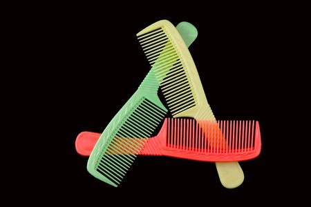 COMBination. Triangle of three coloured plastic combs Stock Photo