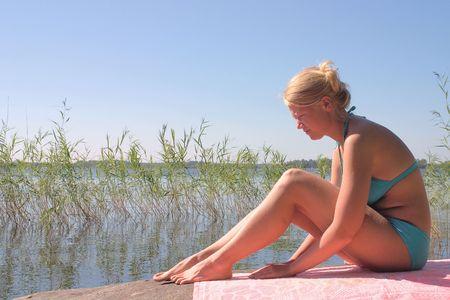 Blonde young lady in blue bikini sitting in the sun