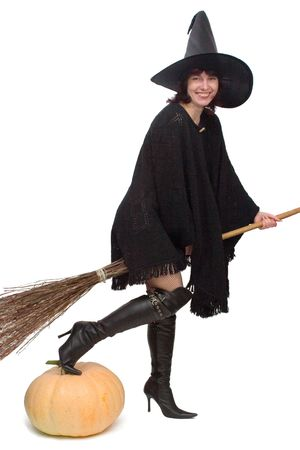 Pretty witch bestridden a broom and ready to fly away, with a toe on large pumpkin