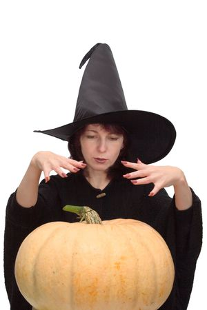 conjuring: Pretty witch in black hat, raising her hands and conjuring over a large pumpkin