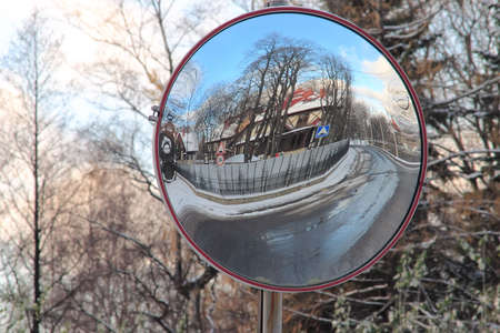 Through the Looking Glass: reflection of road and building in roadsign mirror
