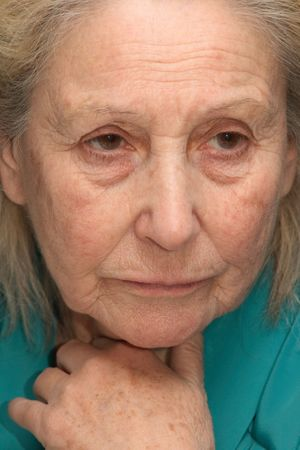 Old woman, absorbed in sad thoughts photo