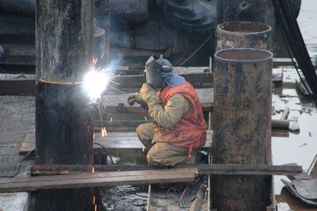 Welder in orange vest welding bridge pier Stock Photo